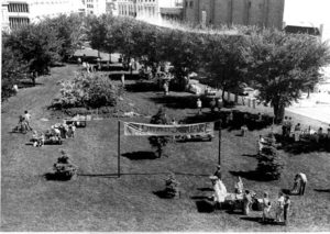 1970s imaage of market square shows a grassy field, young trees, and a cloth banner strung between wooden posts that reads Old Market Square.
